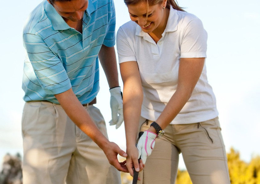 Woman learning how to play golf outdoors